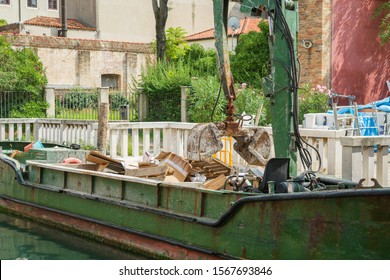 Morning in Venice. A garbage barge equipped with a garbage compactor picks up construction waste from the construction site. Selective focus.