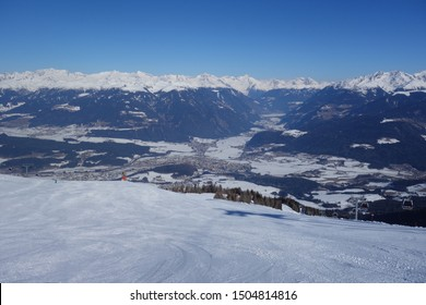 Morning view of freshly prepared skiing slope on a sunny day with blue sky, cable cars and snow-covered mountain peaks in the background (Kronplatz, Italy)