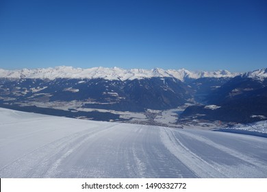 Morning view of freshly prepared virgin skiing slope on a sunny day with blue sky and snow-covered mountain peaks in the background (Kronplatz, Italy)