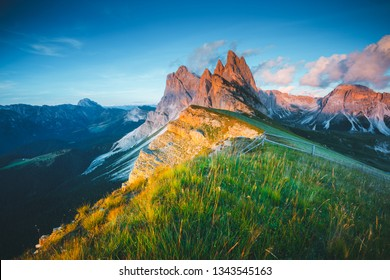 Morning view of the Gardena valley in Dolomite mountains. Location Puez-Geisler National Park, Seceda peak, Italy, Europe. Odle group is the landmark of Val di Funes. Discover the beauty of earth.