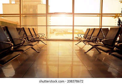 Morning view of international airport indoor hall with glass window. Modern lounge room of airport building with comfortable seats.