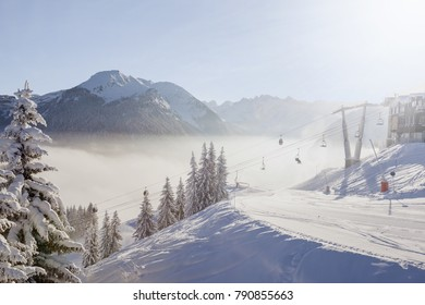 Morning view of Morzine ski resort with snow covered trees, groomed piste, ski lifts and misty mountains in the Portes du Soleil ski area, France.