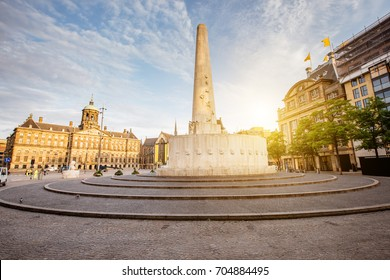 Morning view on the Dam square with Royal palace and monument in Amsterdam city during the sunny weather