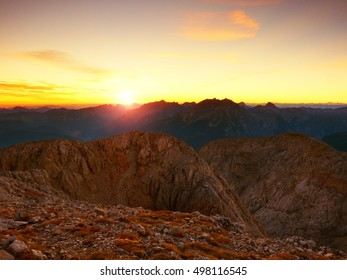 Morning view over Apine  cliff and valley.Daybreak Sun at horizon. Mountains increased from foggy background