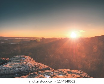 Morning view over sandstone formation into misty valley. Fantastic dreamy sunrise on top of rocky mountain