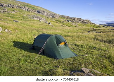 In the morning, the view to the tent in wide landscape. The adventure begins. Campground Eidi, Faroe Islands.