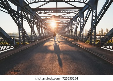 Morning walk across the river. Silhouettes and shadows of the man with dog on the iron bridge.