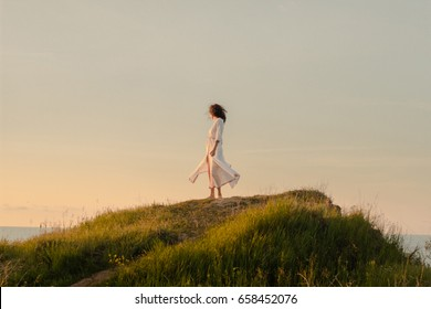 morning walk of beautiful lady in white dress during the sunrise in the sea.