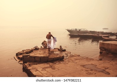 Morning washing in misty indian river Ganga, Varanasi. Calm meditative atmosphere with local people in India.