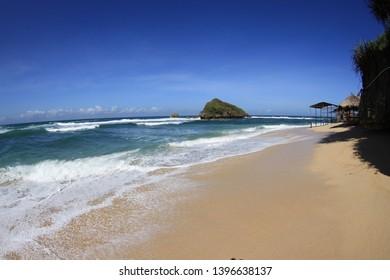 Morning wave crashes into sandy beach in Jogjakarta region.