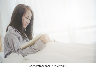 In the morning the white room women are reading.Lady read happily.On white bed there are women studying for knowledge. Warm tone.Do not focus on objects.