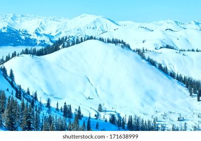 Morning winter mountain landscape with clouds in below valley (Hochkoenig region, Austria)