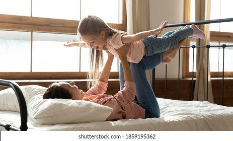 In the morning woman lies in bed play with 6s daughter, hold cute kid, girl stretched arms like airplane wings flying in air have fun with mom. Free time, games with child, dreams about travel concept