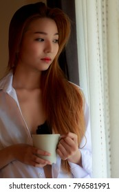 Morning women hold a cup of coffee and look outside to stand near the window.