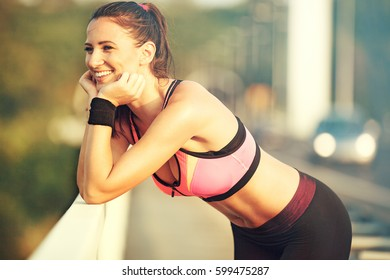 Morning workout. Beautiful young woman exercising on the bridge. Living healthy lifestyle. Relaxing and looking into the distance.