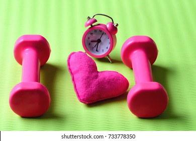Morning workout concept. Dumbbells in pink color next to alarm clock and soft toy heart on green background. Love of sports and early training. Heart decoration near plastic barbells on yoga mat