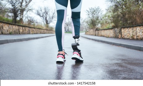 Morning workout. Cropped photo of of disabled athlete woman in sportwear with prosthetic leg standing outdoor