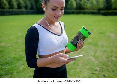 Morning workout. Portrait of young healthy athletic woman in sportswear choosing music set for jogging with mobile application in green summer park outdoors.