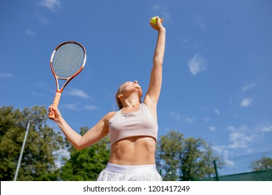 Morning workout routine in outdoor tennis centre. Fitness motivation and muscle training concept. Female athlete starting exercise with tennis innings.