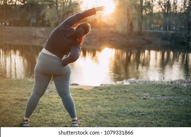 Morning yoga. Young woman doing exercises near the lake,back view. Healthy lifestyle, sport, weight losing, activity concept