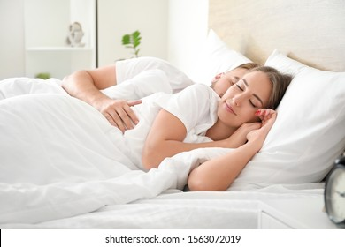 Morning of young couple sleeping in bed
