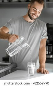 Morning of young man pouring water into glass in kitchen