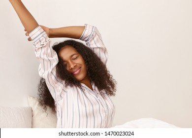 Morning,relaxation and bedtime concept. Indoor image of attractive young African American woman wearing silk striped nightgown stretching body, having pleased joyful happy facial expression