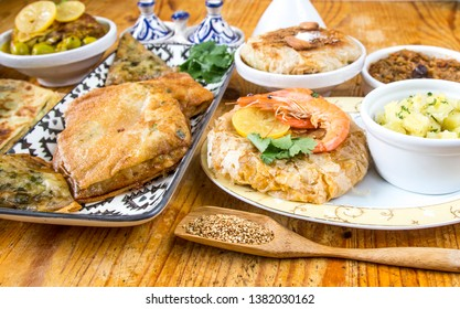 Morocca, arabian specialties. Various of Maghreb cuisine with chicken, seksu Tanjaoui, Couscous, Lamb meatballs with eggas, Honey sweet pastries, Tajine dishes and fresh ingredients.