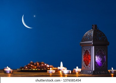 Moroccan, Arabic lantern and dates on on an old wooden table with the night sky and the Crescent moon and the star behind. Greeting card for Muslim community holy month Ramadan Kareem. Free space