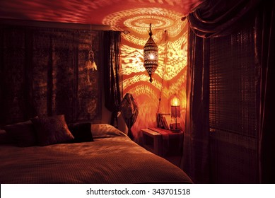 Moroccan bedroom illuminated by Moroccan lamp with golden light pattern on wall/Moroccan bedroom with Moroccan lamp at night