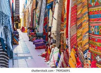 Moroccan carpets with bright colors on sale in the narrow street of Essaouira in Morocco with selective focus