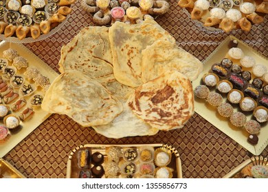 Moroccan dessert trays with various coconut and chocolate truffles and a platter with mufleta, a traditional Moroccan pancake type food, displayed at Middle Eastern parties and often in Jewish culture