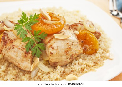 A Moroccan dish, chicken and apricot tajine served over couscous. Tagine is flavoured with ginger, cinnamon, chili and honey.