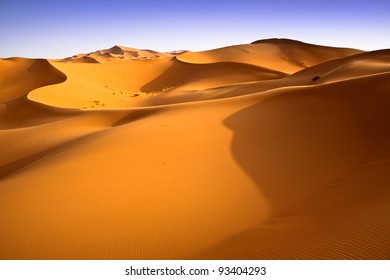 Moroccan dunes landscape with blue sky. Desert background.