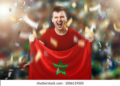 A Moroccan fan, a fan of a man holding a Morocco national flag in his hands. Soccer fan in the stadium.