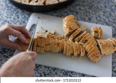 Moroccan fekkas preparation slicing the pre-baked dough on a cutting board using a kitchen knife to toast the pastries and obtain a delicious tea biscuits made with almonds and raisins.