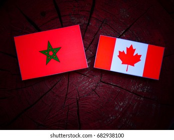 Moroccan flag with Canadian flag on a tree stump isolated