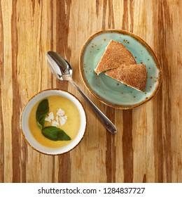 moroccan food, cheese soup dish decorated with basil, on a plate with dark bread, on a wooden table and copy space for text