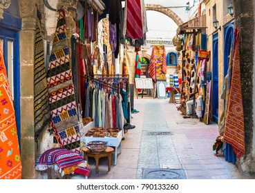 Moroccan handmade crafts, carpets and bags hanging in the narrow street of Essaouira in Morocco with selective focus