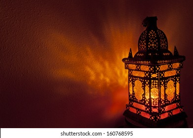 Moroccan lantern with gold colored glass illuminating patterns of light on textured wall in horizontal position. Moroccan lantern with gold colored glass in horizontal position