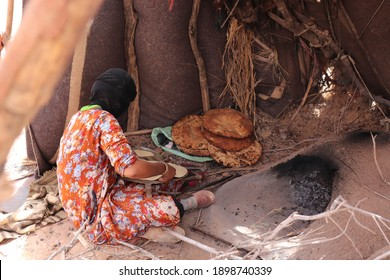 Moroccan local nomadic bedouin family live in nomad tent camp in native berber tradition in african Sahara desert and prepare traditional turkish flatbread in hot oven near Merzouga, Morocco, Africa.