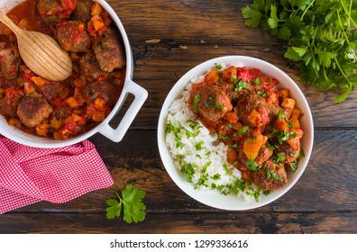 Moroccan meatballs in a spicy sauce with tomatoes and dried apricots and boiled rice. White casserole and bowl on wooden rustic table, top view