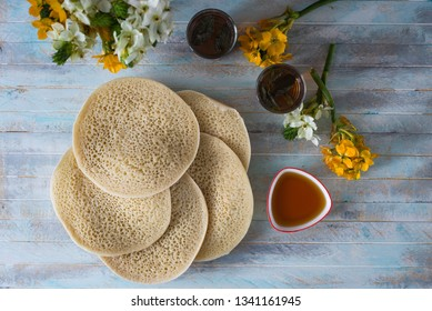 Moroccan pancakes Baghrir or crapes with 1000 holes served with honey, tea with nana , with background with flowers top view , flatlay with copy space