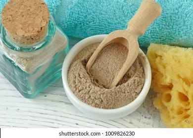 Moroccan rhassoul clay in a bowl with a spoon on wooden background
