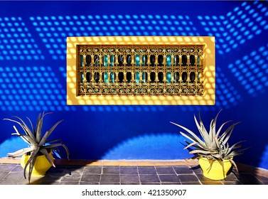 The Moroccan still life: two yellow flower pot of aloe on the background of blue wall with yellow window with bars