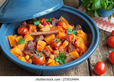 Moroccan Tagine with beef, chickpeas,  pumpkin and cherry tomatoes on a wooden table. Selective focus