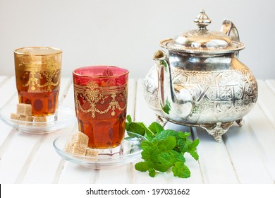 Moroccan tea with mint and sugar in a glass on a white table with a kettle