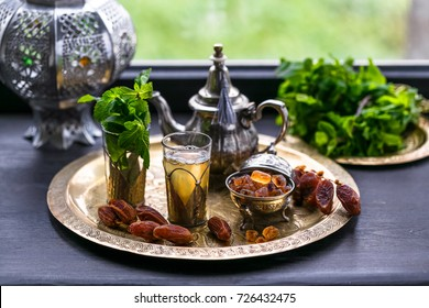 Moroccan tea with mint and sugar in a glasses on a copper plate with kettle