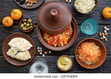 Moroccan traditional tajin and various snacks on dark wooden table. Carrot Salad, Couscous, Olives, Hummus. Flat lay