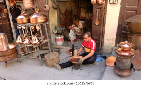 Morocco, the city of Fez, March 12, 2019: Tinker coppersmith demonstrates his work and his goods in his workshop on one of the city's shopping streets.